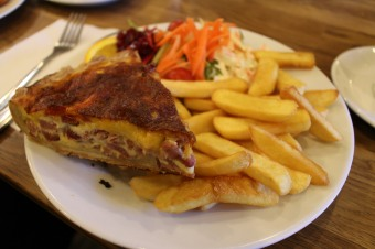 Ham and tomato quiche with chips and salad