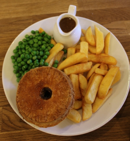 Steak pie with gravy, chips and peas